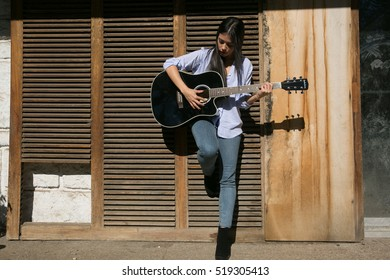 girl posing with jeans and a guitar
