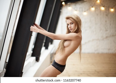 girl posing in photostudio with white wall