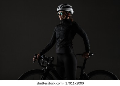 Girl posing with roadbike. White protective helmet and fashion sunglasses. Side lit cyclist against dark background.