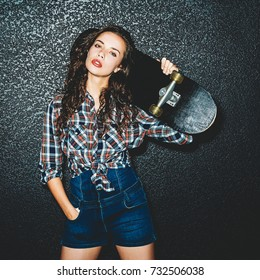 Girl posing with skateboard over black wall