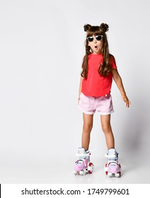 girl posing standing on roller skates, in a red t-shirt and shorts and a fashionable hairstyle and sunglasses, in the Studio and looks in surprise with her left hand slightly to the side takes