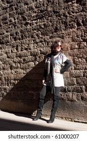 Girl posing at the stone wall