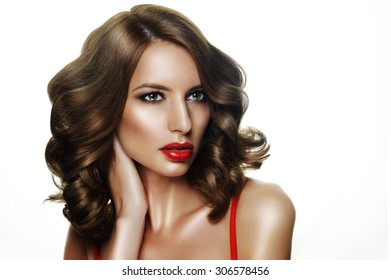 .girl posing in the studio. Behind a white background. her lips were dyed bright red lipstick. Curly hair, well-groomed. She has a pure healthy skin.