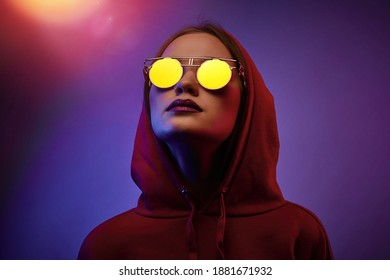 Girl posing in a studio in a trendy neon light. Woman in round sunglasses and hoodie with colorful light effects.