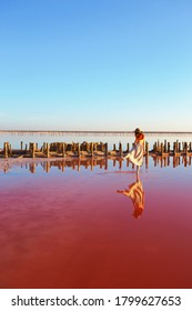 girl posing at sunset on the famous pink salt lake. reflection in the lake