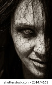 Girl possessed by the devil looks at you out of darkness. Black and white