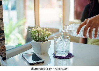 Girl poured bottled water on the table in cafe in the morning on Monday. - Shutterstock ID 719871004