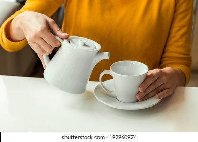 girl is pouring tea from beautiful white teapot into a white cup