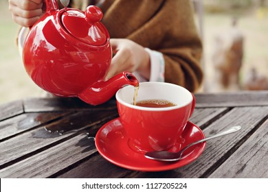 Girl pouring tea from red tea pot at outdoor. cup, outdoors. Young woman drinking tea at garden.