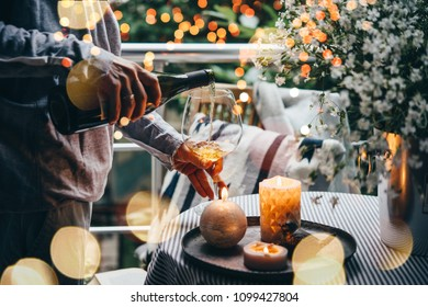 Girl pouring wine on a terrace. Cozy evening and relax concept