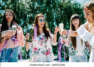 Girl pours champagne into glass. Beautiful happy stylish sexy young girls on sand beach. Glasses decorated with ribbons flowers. Party in Style boho. Maiden evening Hen-parties. Bachelorette. Close up