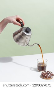 The girl pours coffee from a coffee pot in a glass. Minimalistic concept.