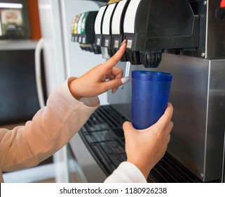 Girl pours a fizzy drink into a blue glass from a vending machine