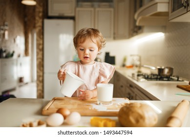 Girl pours milk into a glass, pastry preparation