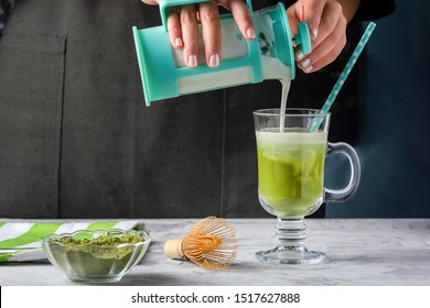 A girl pours milk into a glass with matcha green tea. The process of making healthy latte. Cropped photo.