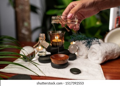 A girl pours oil from a jar of aromatic oils into a wooden bowl located on a terry towel next to which are transparent spheres, a twisted terry towel of white color and a sprig of lavender