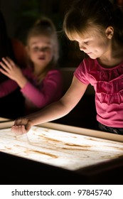 Girl pours sand on table from her hand in classroom with friends