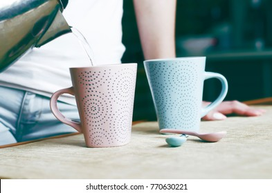 the girl pours water from a teapot into a mug