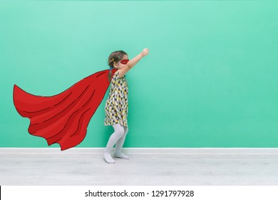 Girl power. Child in the form of a superhero. Hand-drawn raincoat and mask. Funny little girl on a turquoise background with a place for text.