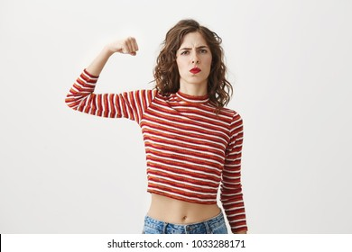 Girl power. Serious cool slender woman in cropped top raising hand while showing muscle, trying to look dangerous while frowning and standing over gray background. You came in wrong place.