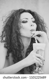 Girl Powered. Issues face girls. Portrait of magnificent sexy pensive cute young woman with bright makeup brown curly long hair looking away sipping cocktail through straw holding glass on light