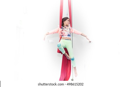 Girl practices circus class on red silk