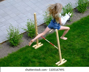 Girl practices for hobby horse championship in the yard.