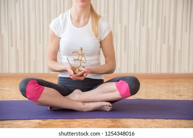 A girl practices yoga in a gym and sits in a lotus position with the sign of mantra om
