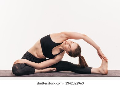 The girl practices yoga in the studio on a white background. Included in nirvana. Soothes breathing. Releases the chakras.