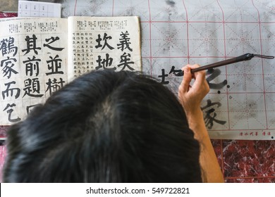 girl practicing chinese callingraphy using a brush pen in her hand