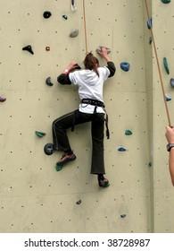 A girl practicing climbing skills on a climbing wall