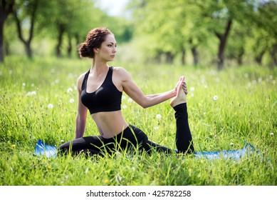 Girl practicing yoga in the apple garden