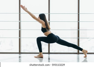 Girl practicing yoga at the gym windows.