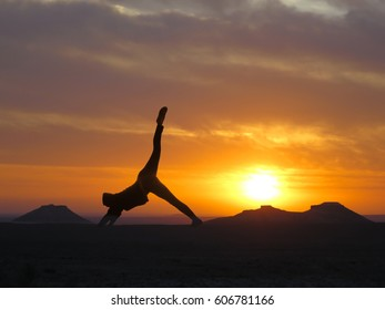 Girl practicing yoga on a background of mountains and sunset