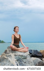 Girl practicing yoga on the rocks against the blue sky and the azure sea. Woman raises her arms to the sky in namaste posture and sits in a lotus pose.