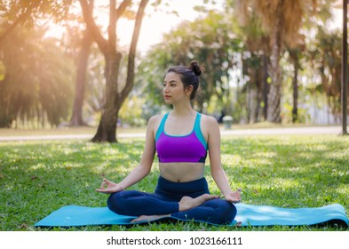 The girl practicing yoga in the park.