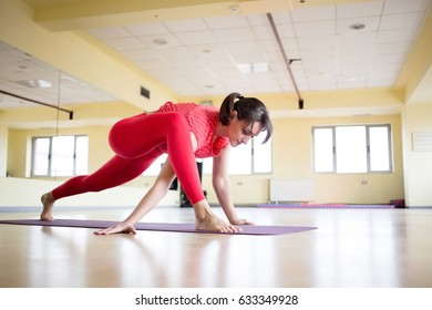 Girl practicing yoga in studio. Attractive female doing mat exercise and posing in modern bright fitness center.