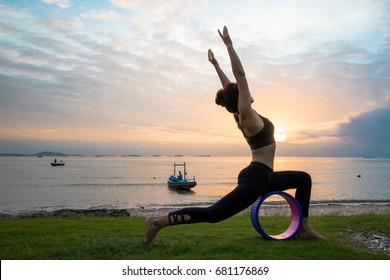 A girl practicing yoga with a wheel She was at the beach at sunset time. Yoga practice helps to focus on those who practice and help keep the body healthy. Supplement blood circulation Make good healt