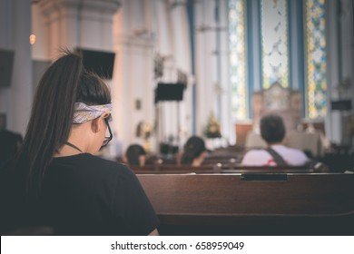 A girl is praying in the church.