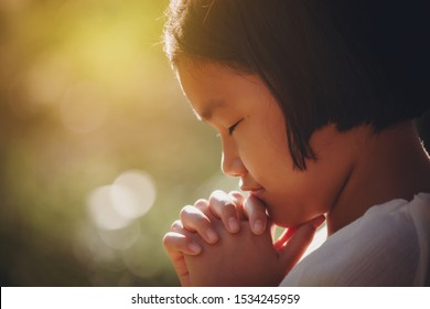 Girl praying hand faith jesus promise Pray for god blessing wishing have better life Christians together with flare sunlight at sunset