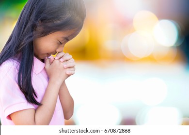 Girl praying on the morning in church.Asian girl hand praying,Hands folded in prayer concept for faith,spirituality and religion.