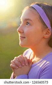 Girl praying with opened eyes at sunset light