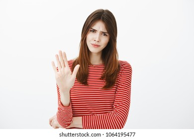 Girl prefers open relationship, hate talking about marriage. Displeased annoyed woman in striped outfit, pulling palms towards camera in stop or no gesture, frowning, rejecting offer with dislike