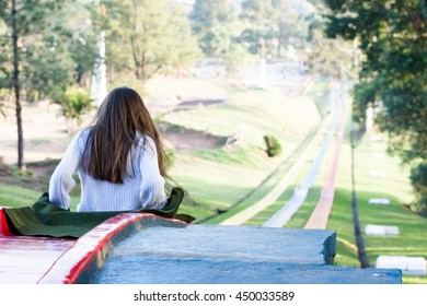 Girl prepares to slide on red toboggan