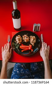 The girl is preparing for dinner. Top view. Baked meat with paprika and salad on a black plate and a bottle of wine on a red table.