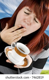 Girl preparing to drink her cup of coffee. Tired. Studio shot.