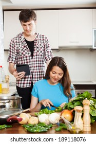 Girl preparing food while man looking at eBook in home kitchen