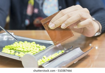 The girl is preparing  green pills on the medicine brown.