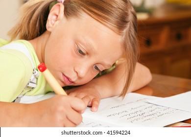 Girl preparing her homework for school writing in her exercise book