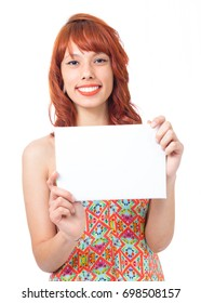 Girl is presenting an offer. Advertising. Redhead woman is wearing a colorful summer dress. Fashion and style. Vacation and summer.